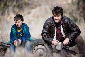 """Le jeune Nikola (Eldar Rešidović) et Mambrú (Benicio Del Toro); un homme au coeur de père. Scène du film """"A perfect day"""""""